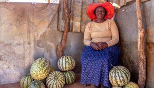 Female farmer sitting with goods